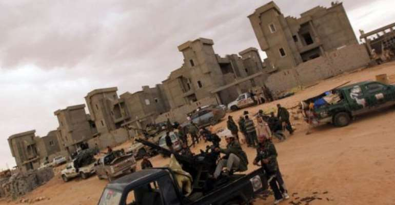 Libyan National Transitional Council (NTC) fighters gather at an outpost south of Bani Walid.  By Karim Sahib (AFP/File)