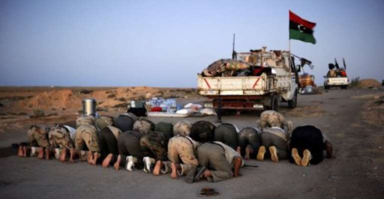 Rebel fighters pray on the last day of the fasting month of Ramadan.  By Eric Feferberg (AFP)