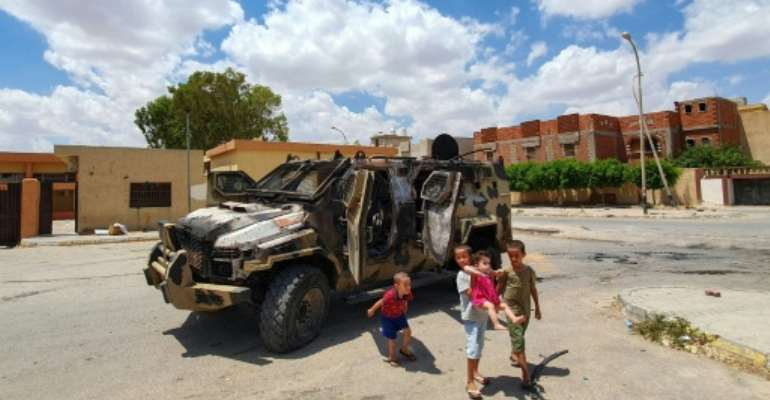 Libyan children play next to a burnt out vehicle belonging to forces loyal to strongman Khalifa Haftar in Gharyan, 100 kilometres (60 miles) southwest of Tripoli, earlier this year; the UN has called for a humanitarian truce.  By Mahmud TURKIA (AFP/File)