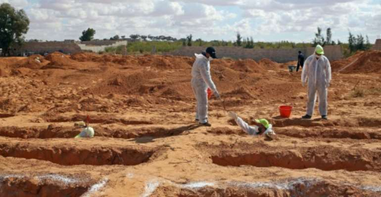 Libyan experts exhume human remains from mass graves in Tarhuna, southeast of the capital Tripoli, on Wednesday.  By Mahmud TURKIA (AFP)