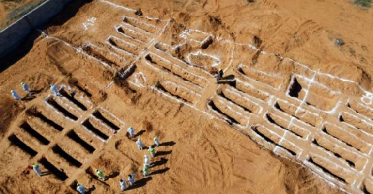 Libyan experts exhuming human remains from mass graves in Tarhuna, southeast of the capital Tripoli, on October 28.  By Mahmud TURKIA (AFP/File)