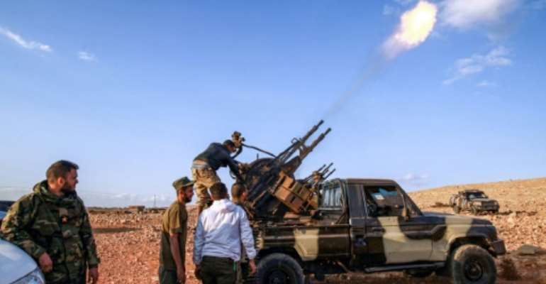 Libyan fighters loyal to eastern strongman Khalifa Haftar fire guns during a funeral of a comrade in November 1, 2020; Haftar has urged his troops 'drive out' Turkish forces.  By Abdullah DOMA (AFP)