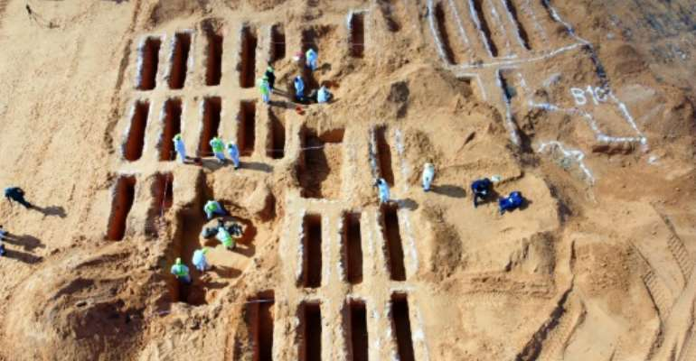 Libyan members of the team excavating mass graves investigate remains in Tarhuna, where 17 bodies have been discovered.  By Mahmud TURKIA (AFP)