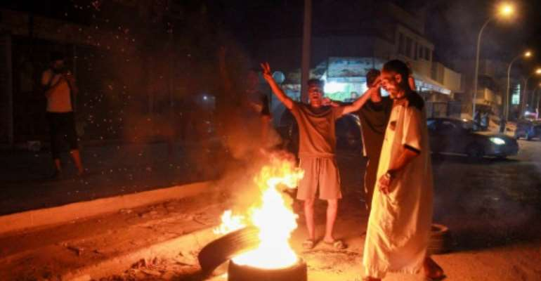 Libyan youth block a road with burning tyres in the eastern city of Benghazi to protest against poor public services and living conditions.  By Abdullah DOMA (AFP)