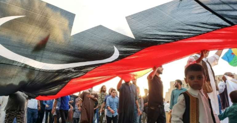 Libyans march in Tripoli with a giant national flag during a September demonstration in support of the UN-recognised government and against strongman Khalifa Haftar who has led an offensive on the capital city since April.  By Mahmud TURKIA (AFP)