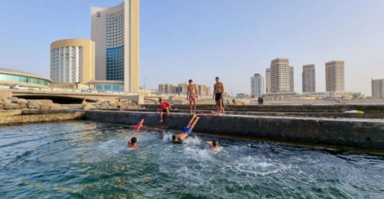 Libyans swim in the Mediterranean at the capital Tripoli's waterfront. Libya's infrastructure has been devastated by a decade of conflict, state collapse and neglect since the 2011 overthrow and killing of dictator Moamer Kadhafi.  By Mahmud TURKIA (AFP)