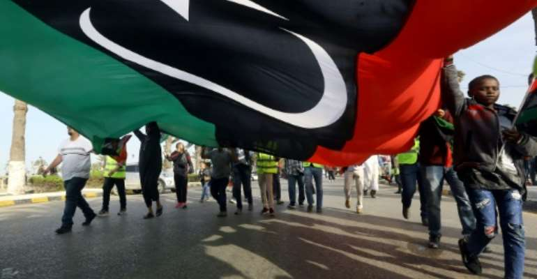 Libyans wave a giant national flag during a demonstration in Tripoli on Friday, in protest against strongman Khalifa Haftar.  By Mahmud TURKIA (AFP)