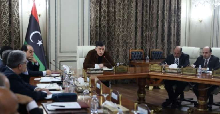 Libya's UN-recognised Prime Minister Fayez al-Sarraj (C) presided over a cabinet meeting where the implementation of a military deal with Turkey was 'unanimously approved'.  By - (AFP)