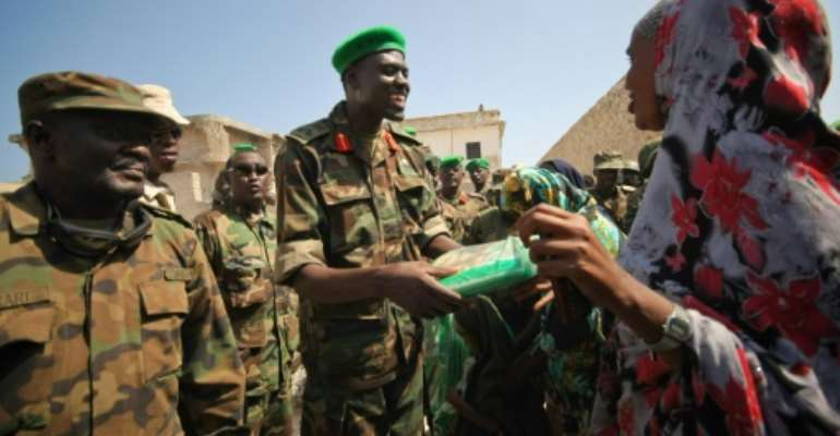 'Lion': Major General Paul Lokech, a brigadier at the time, handing out mosquito nets to civilians in Mogadishu in 2012.  By STUART PRICE (AU-UN IST/AFP/File)