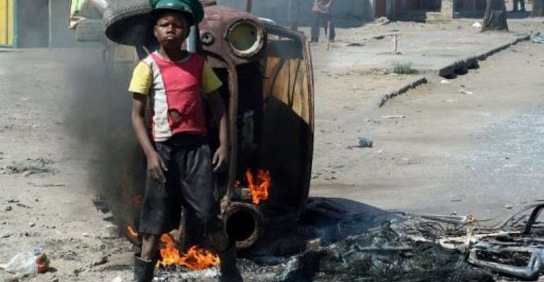 A protester stands near a burning car in Maputo amid unrest over poverty on September 2, 2010.  By Sergio Costa (AFP/File)