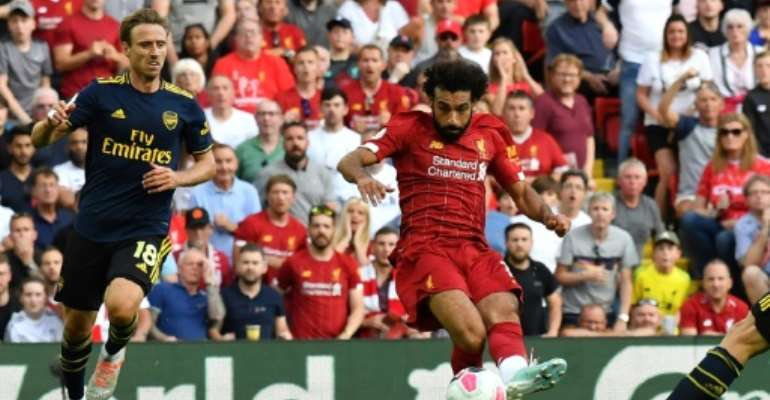 Liverpool's Egyptian midfielder Mohamed Salah (C) shoots to score his second goal, Liverpool's third during the English Premier League football match between Liverpool and Arsenal at Anfield in Liverpool, north west England on August 24, 2019..  By Ben STANSALL (AFP)