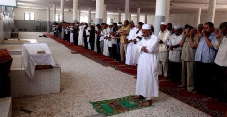 Friends and relatives pray over body of Abdelbaset Ali Mohmet al-Megrahi.  By Mahmud Turkia (AFP)