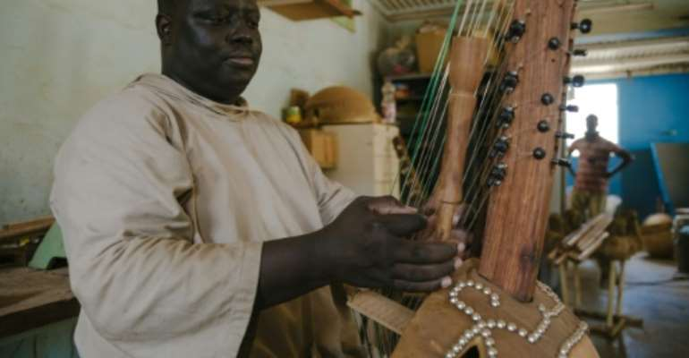 Long-necked kora harps are made with a calabash gourd as the soundbox.  By CARMEN ABD ALI (AFP)