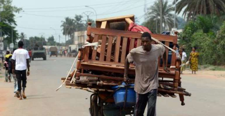 A man pulls a cart full of pieces of furnitures he looted as he walks near a convoy of French soldiers on February 9, 2014 in Bangui.  By Issouf Sanogo (AFP)