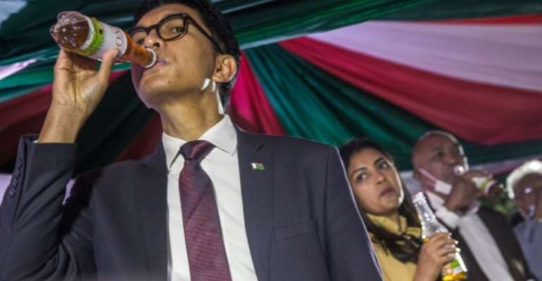Madagascar's President Andry Rajoelina sips Covid Organics, which he touts as a remedy for coronavirus.  By RIJASOLO (AFP/File)