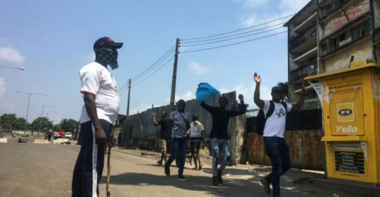 Makeshift barricades emerged in Lagos run by men in civilian clothes carrying machetes and sticks who present themselves as