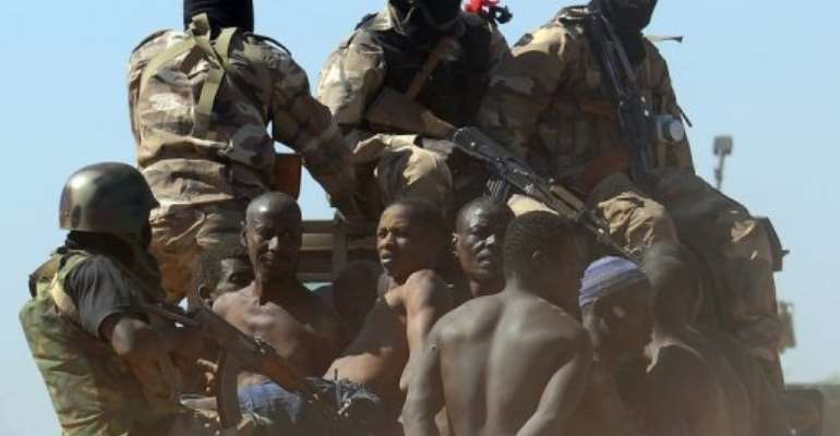 Malian soldiers transport a dozen suspected Islamist rebels on February 8, 2013 after arresting them north of Gao.  By Pascal Guyot (AFP/File)