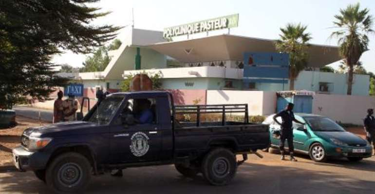 Police officers stand in front of the quarantined Pasteur clinic in Bamako on November 12, 2014.  By Habibou Kouyate (AFP/File)