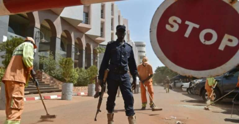 A Malian police officer stands guard as municipal workers clean outside the Radisson Blu hotel in Bamako on November 22, 2015, two days after a deadly Jihadist attack.  By Issouf Sanogo (AFP/File)