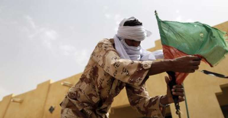 A soldier of the rebel National Movement for the Liberation of Azawad (MNLA) fixes a MNLA flag at their headquarters on July 27, 2013 in the northern Malian city of Kidal.  By Kenzo Tribouillard (AFP/File)