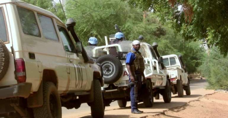 Malian police patrol with German UN mission in Mali (MINUSMA) peacekeping forces on May 18, 2016 in Gao, northern Mali.  By SOULEYMANE  AG ANARA (AFP/File)