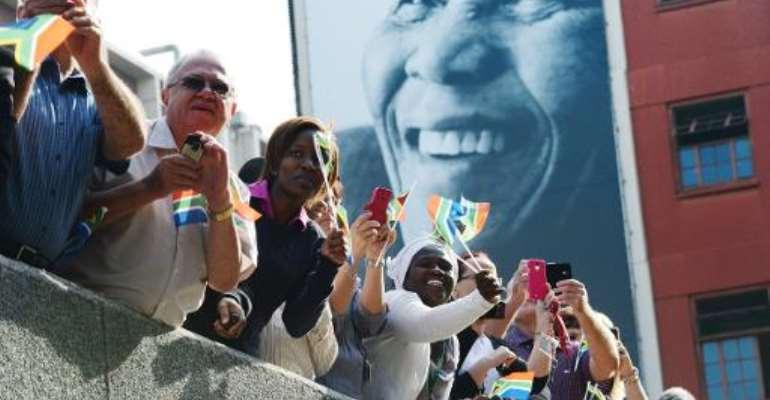 South Africans watch Nelson Mandela's funeral cortege on Madiba Street in Pretoria on December 11, 2013.  By Roberto Schmidt (AFP)