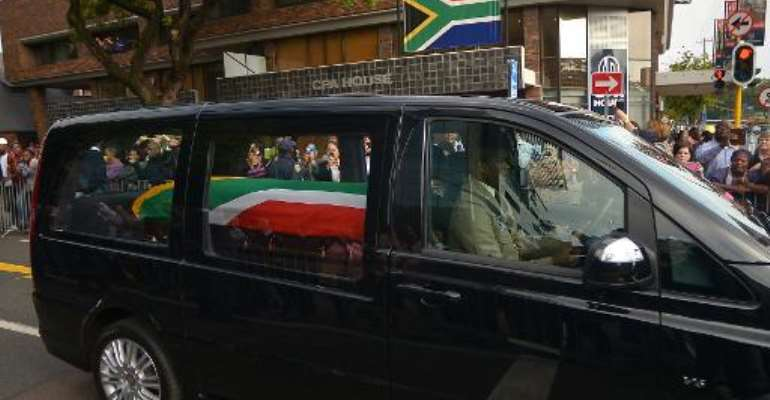 The funeral cortege of South African former president Nelson Mandela drives through the streets in Pretoria on December 11, 2013 to the Union Buildings to mark the start of a three-day lying in state.  By Filippo Monteforte (AFP)