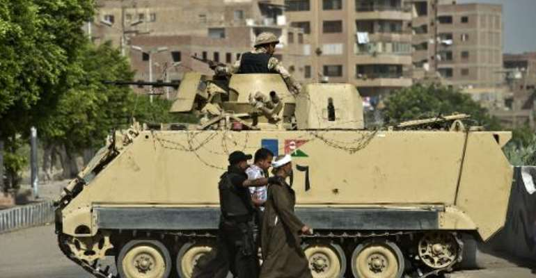 An Egyptian armed policeman arrests two people on the outskirts of Cairo on September 19, 2013.  By Khaled Desouki (AFP/File)
