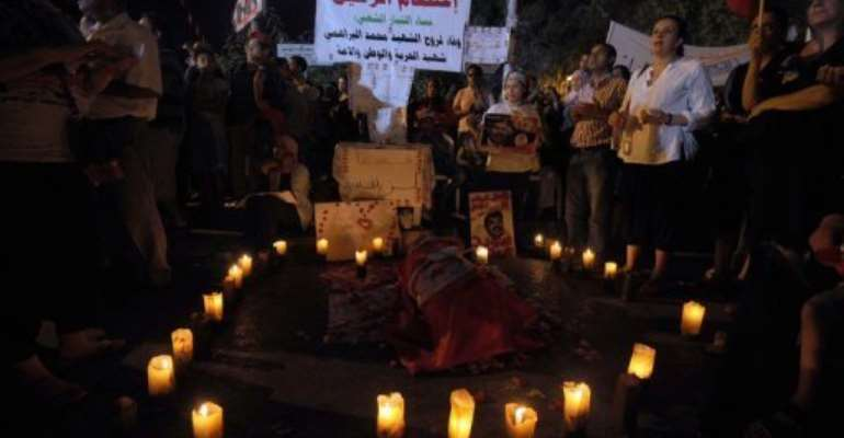 Tunisian protesters light candles by a symbolic coffin on August 4, 2013 in Tunis.  By Fethi Belaid (AFP/File)