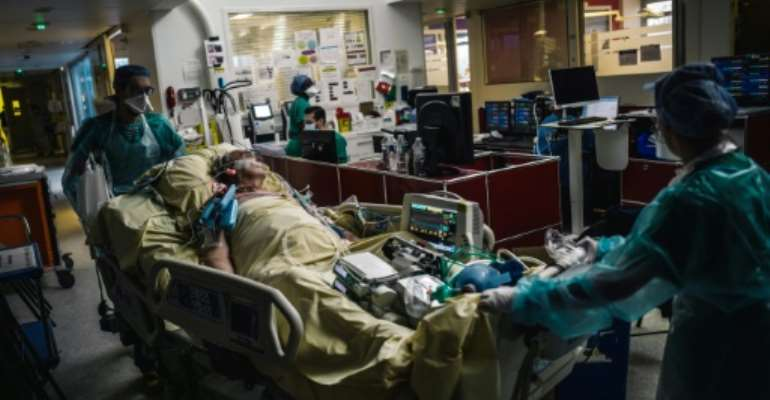 Medical staff transport a patient at the intensive care unit of Paris's Lariboisiere Hospital.  By LUCAS BARIOULET (AFP)