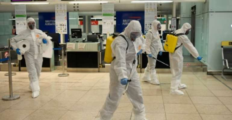 Members of Spain's Military Emergencies Unit (UME) carry out a disinfection at Josep Tarradellas Barcelona-El Prat airport.  By Josep LAGO (AFP)