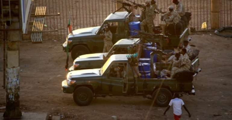 Members of Sudan's intelligence services shoot bullets in the air at the headquarters of the Directorate of General Intelligence Service in the Riyadh district of the capital Khartoum.  By ASHRAF SHAZLY (AFP)