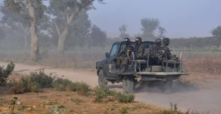 Members of the Cameroonian Rapid Intervention Force patrol on the outskirt of Mosogo in the far north region of the country where Boko Haram jihadists have been active since 2013, on March 21, 2019.  By Reinnier KAZE (AFP/File)