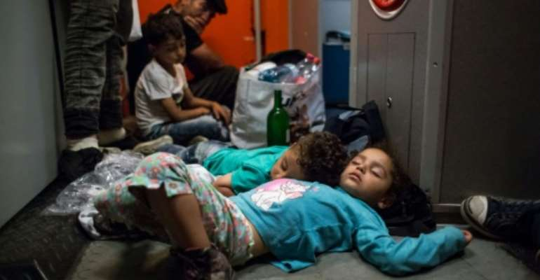 Migrant children sleep on the floor on the train from Budapest to Munich at the Austrian - Hungarian border in Hegyeshalom on August 31, 2015.  By Vladimir Simicek (AFP)