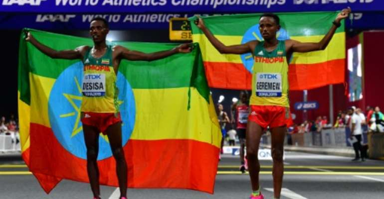 Migrant workers turned out in force to support runners from their native countries at the World Athletics Championships men's marathon in Doha, which saw Ethiopia's Lelisa Desisa (L) win gold.  By Giuseppe CACACE (AFP)
