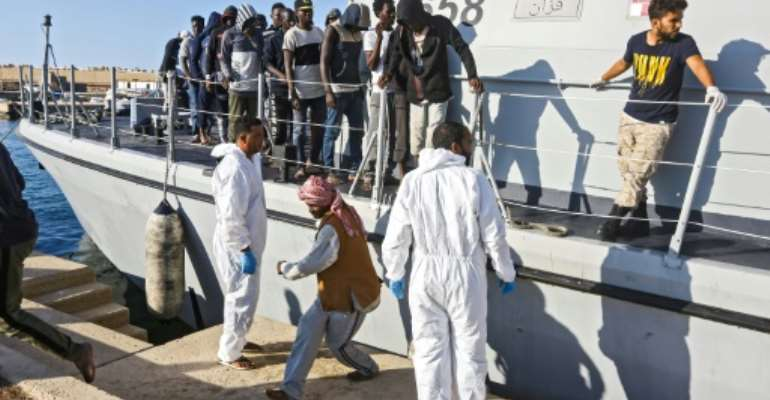 Migrants disembark in October 2019 from a Libyan coast guard ship in the town of Khoms, part of the instability that has led the United States to impose sanctions on smugglers.  By Mahmud TURKIA (AFP/File)