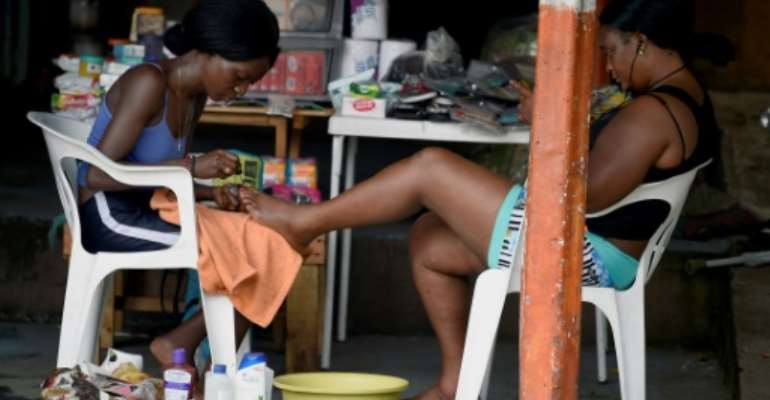 Migrants from Haiti and African countries stuck in the Mexican town of Tapachula do menial work to get by, such as giving pedicures.  By ALFREDO ESTRELLA (AFP/File)