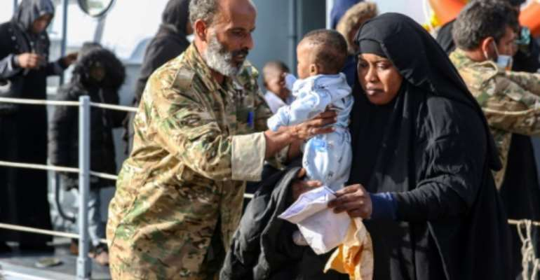 Migrants rescued off the coast of Al-Khums, east of the Libyan capital, disembark a coastguard vessel at Tripoli's naval base on Wednesday.  By - (AFP)