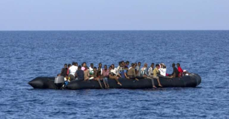 Migrants wait to be rescued by Italian coast guard in the Mediterranean Sea, nautical miles from the Libyan coast, on August 6, 2017.  By Angelos TZORTZINIS (AFP/File)