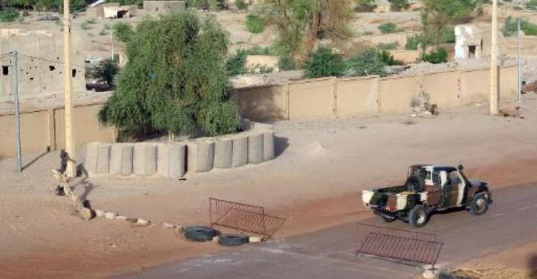 A Malian military vehicle drives past a checkpoint on July 26, 2013 at one of the entrances to Timbuktu.  By Dorothee Thienot (AFP/File)