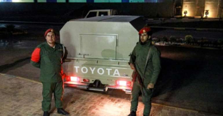 Military police loyal to strongman Khalifa Haftar stand guard earlier this month outside a vehicle allegedly containing arrested Syrian mercenaries.  By Abdullah DOMA (AFP)