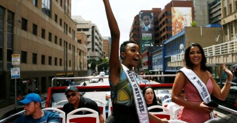 Miss Universe, Zozibini Tunzi (L) waved to crowds who came out to greet her and celebrate her victory.  By Phill Magakoe (AFP)