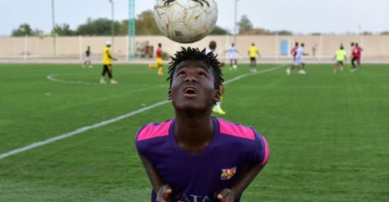 Mohamed Diaby, a 16-year-old from Ivory Coast who hopes to migrate to Europe, training with Nassara Agadez, a team in Niger's second division.  By ISSOUF SANOGO (AFP)
