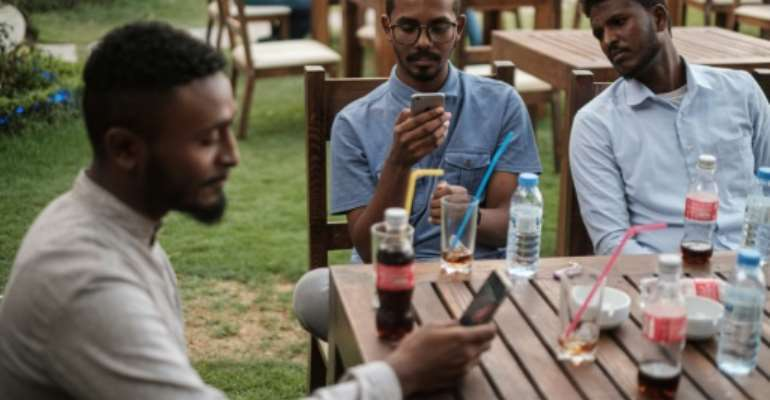 Mohamed Omar (L) sits with his friends at a cafe in an upscale district of Sudan's capital on June 17, 2019.  By Yasuyoshi CHIBA (AFP)