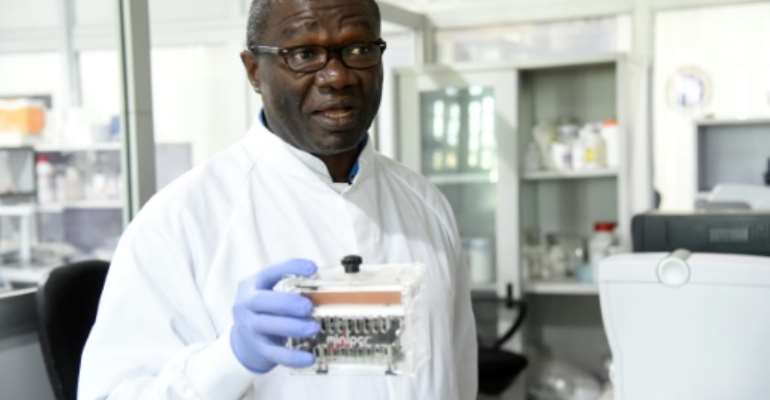 Molecular biologist Christian Happi, head of the ACEGID genomics lab, holds a thermal cycler, which amplifies genetic segments of the virus.  By PIUS UTOMI EKPEI (AFP)