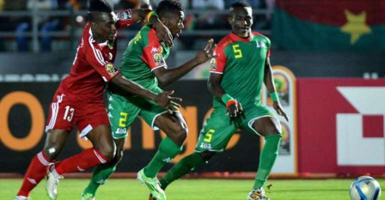 Congo's forward Thievy Bifouma (L) challenges Burkina Faso's defenders Steeve Yago and Mohamed Koffi (R) during the 2015 African Cup of Nations group A football match in Ebebiyin on January 25, 2015.  By Khaled Desouki (AFP)
