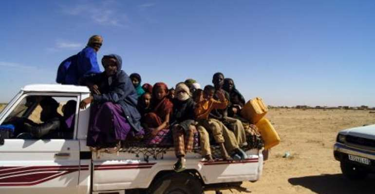 Malian refugees ride in the back of a truck transporting them on a dirt road from Timbuktu to the Mauritanian town of Fassala on January 18, 2013.  By - (Al-Akhbar News Agency/AFP/File)