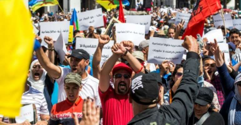 Moroccan demonstrators hold their hands up in a bound gesture while shouting slogans as they wave the Berber, or Amazigh, flag during a protest march against the jailing of Al-Hirak al-Shaabi or