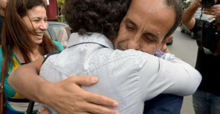 Ali Anouzla (right) hugs a relative after he is freed on bail in Rabat on October 25, 2013.  By Fadel Senna (AFP)