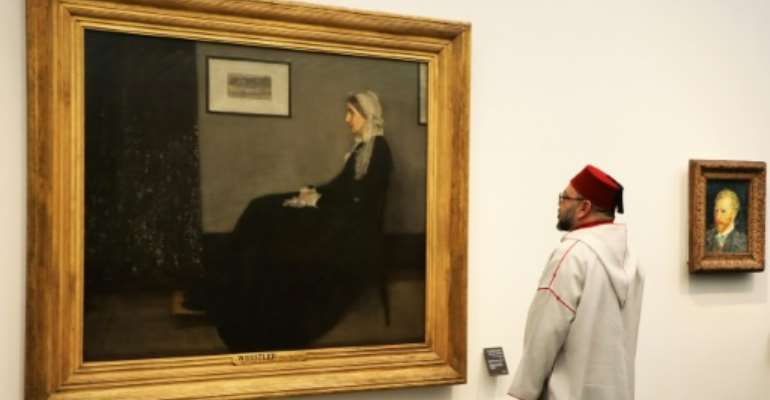 Moroccan King Mohammed VI looks at a painting titled